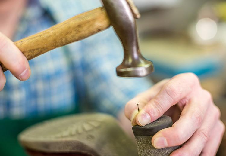 Eine Schuhsohle wird per Hammer repariert