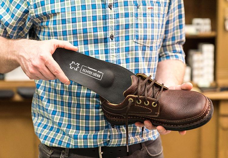 Eine Ledersohle wird in einen Schuh eingesetzt